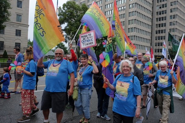 group of people in blue T-shirts and carrying rainbow flags that say proud to be a Catholic teacher
