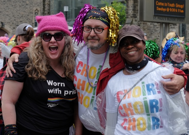 group of three pose for a picture, two are wearing Tshirts that say choir Choir Choir.