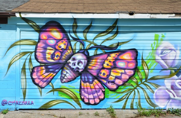 colourful butterfly mural on a garage door, blue background