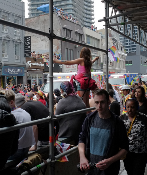 people watching pride parade on yonge street in toronto, scaffolding for construction, people on roofs, people walking by on sidewalk