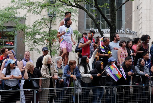 crowds watching the pride parade, all ages, some standing on planters in the middle of Yonge Street, College Park building behind them