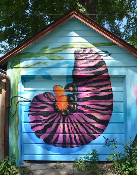 a large pink and black caterpilar curled up on a garage door - mural