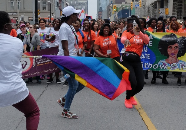 dyke march 2018 - dancing women in orange T-shirts, rainbow sisters, one is waving a rainbow flag