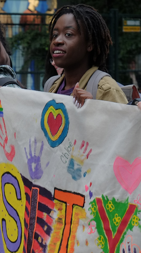 young black woman holding a banner in the dyke parade