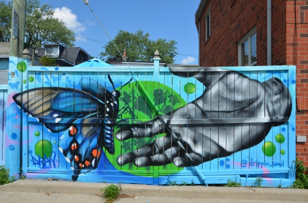 a mural by @drippin_soul of a hand reaching towards a blue butterfly