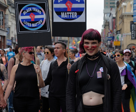 women carrying signs black lives matter and black trans lives matter in dyke march in Toronto, marroon coloured hair and make up