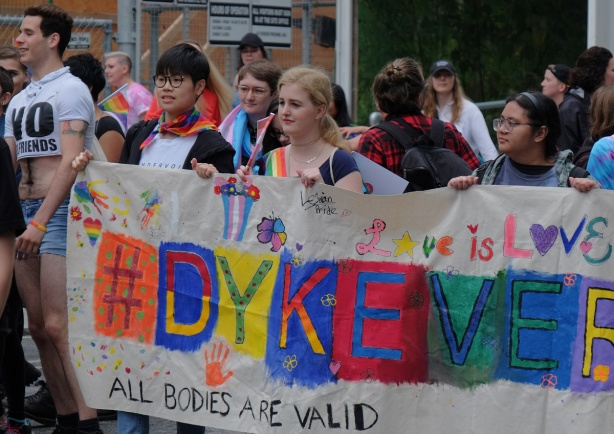 dyke march 2018, banner that says dykeversity, lots of hand prints and hearts decorating it, women carrying it,