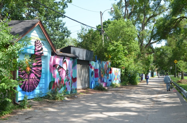 a lane with many painted garage doors, butterfly murals, summer time, green leaves, lots of trees, two people walking