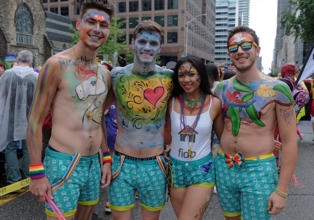 a group of four young people from the fido section of the pride parade, in teal shorts, covered with colourful body paint hearts and stars and rainbows