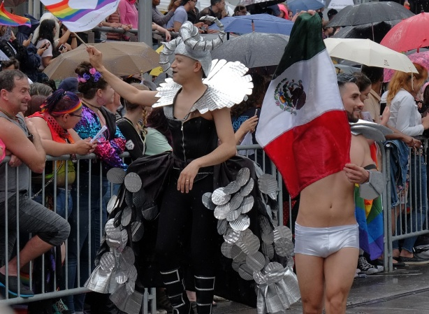 two men walking in the pride parade, one in a skimpy tight silver pair of short pants and carrying a Mexican flag, the other in drag in a black and silver costume, long dress, with hat with silver horns on it