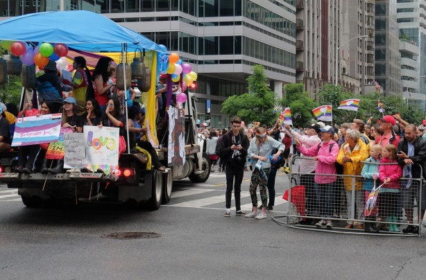 a float enters the pride parade while spectators watch from the sidewalk, behind barricades