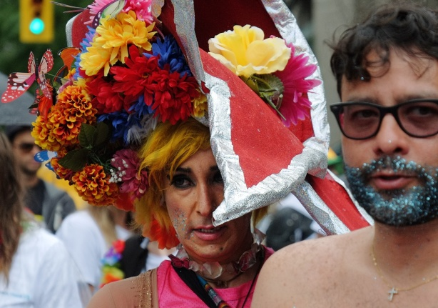 two men, one with a makeup sparkly beard and moustache in blue and silver and one in drag with a loarge red hat covered with flowers