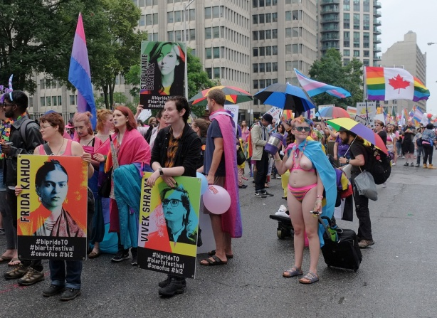 getting ready for the pride parade, a topless woman stands near a group carrying posters, one with Frida Kahlo on it and the other with Vivek Shraya