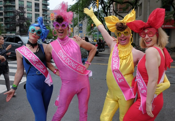 four people in stretchy tight fitting unitards, a pink, a blue, a yellow and a red, all have sashes that say Ding Dong Girls