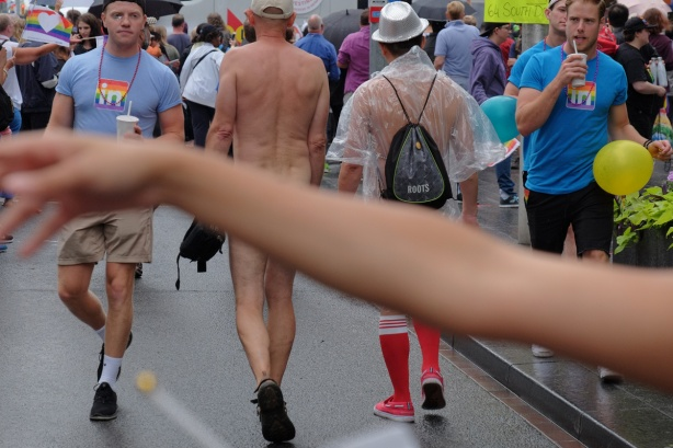 an out of focus arm covers the bare bottoms of two naked men as they walk past