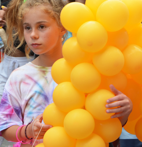 a young girl holding a bunch of yellow balloons