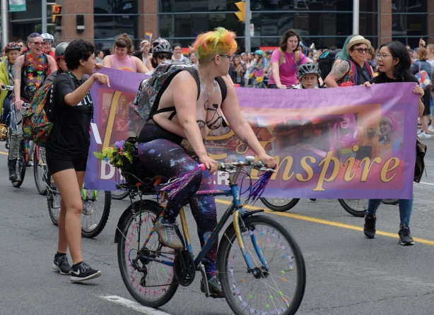 dyke march 2018, dykes on bikes - bare breasted woman with yellow and orange hair, on a bike in front of two women carrying a purple banner with the word inspire on it