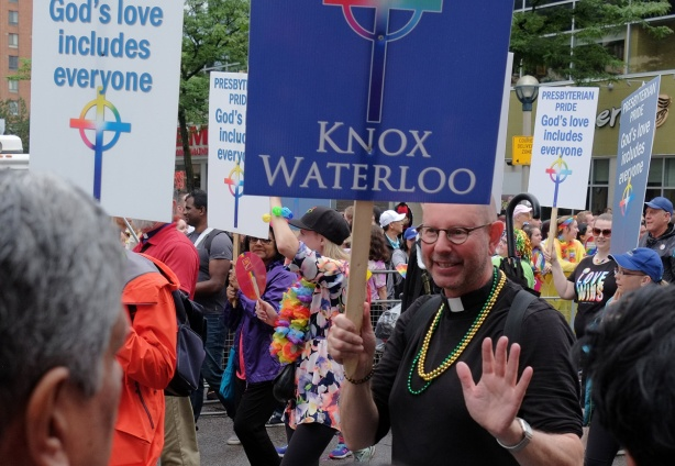 marchers from the presbyterian church walking in the pride parade, man holding a sign that says Knox Waterloo, in clericals, with beaded necklaces around his neck