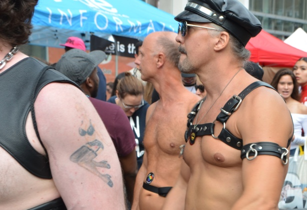 men with no clothes except for black leather harnesses and straps and a black cap