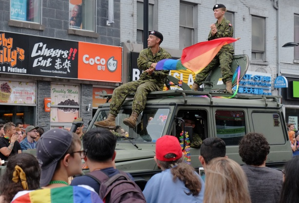 two military personnel sitting on top of a green jep with rainbow flags as they drive in the pride parade