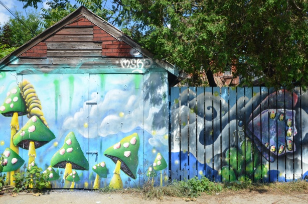 mural by mska on a garage door and fence, green and yellow toadstools