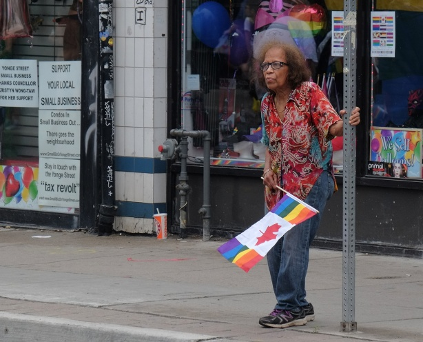 an older woman stands beside a pole on the sidewalk as she watches the dyke march, she's holding a rainbow flag