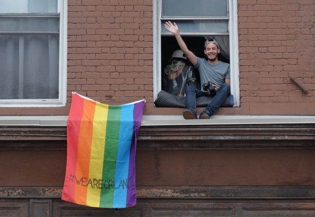 dyke march 2018 - a young man sits on the ledge of an open upper storey window on Yonge street, rainbow flag with #weareorlando (we are orlando) written on it