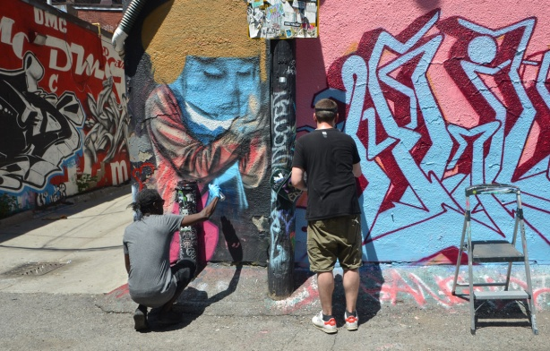 elicser paints a person on a wall, another man is beside him, also spray painting street art in Graffiti Alley