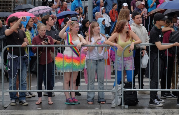 behind metal barricades, people watching the pride parade