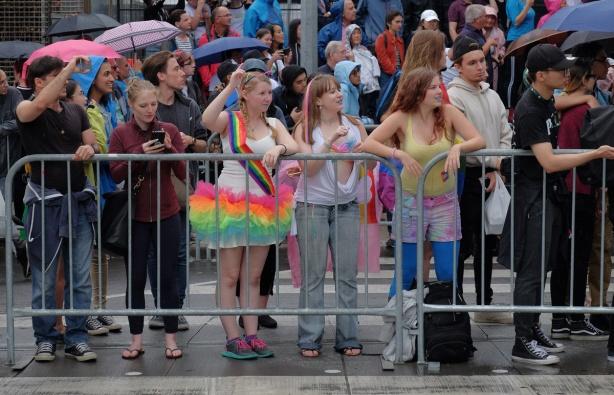 behind metal barricades, people watching the pride parade