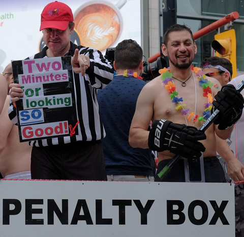 on a float at the pride parade, sign says penalty box. Man in referee shirt with a sign that says Two minutes for looking so good. He is pointing at the camera