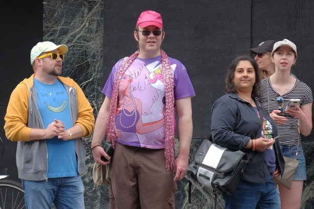 people watching the Dyke March, two men and two women. One man in pink baseball hat and My Little Pony T-shirt
