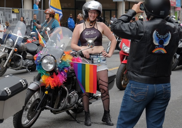 dyke march 2018 - a break in the parade is time for a photo op of motorcycle with passenger wearing helmet and fishnet stockings.