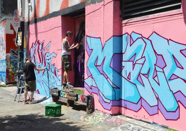 a street art piece in progress, man spray painting,