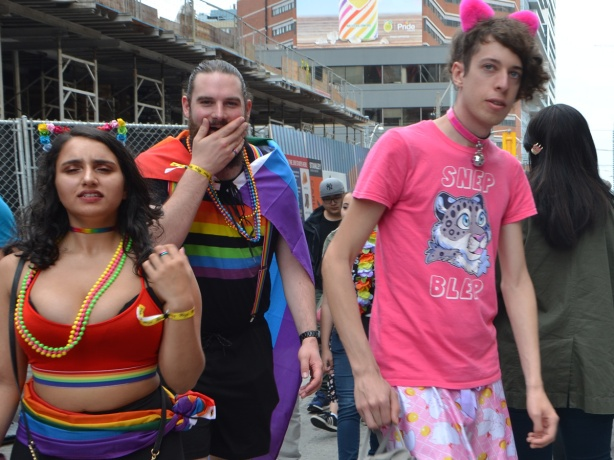 a young man with pink t shirt and fuzzy pink ears, another man with a rainbow flag on his back and his hand over his mouth