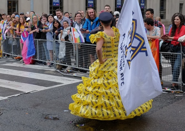 a man wears a dress made of yellow police caution tape in a parade