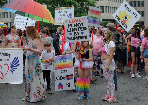 polyamory group, men, women and children, with colourful clothes and signs waits their turn to join the pride parade