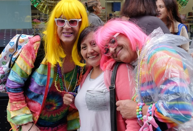 two men in drag pose for a selfie with a woman, one man in bright yellow wig and the other in bright pink with flashy bright clothes to match