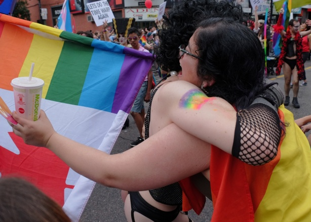 two people hugging at the pride parade, one is a man dressed in a Rocky Horror outfit and the other is a woman with a rainbow flag and a Mcdonalds drink in her hand
