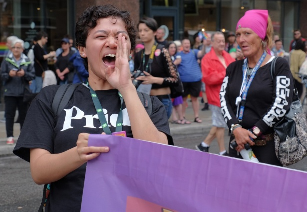 a young woman in black Pride T-shirt, holds a purple banner and is yelling dyke march 2018