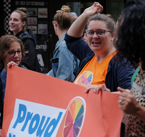 dyke march 2018 - a woman holds an orange Proud NDP sign in the parade, one arm reaching upwards
