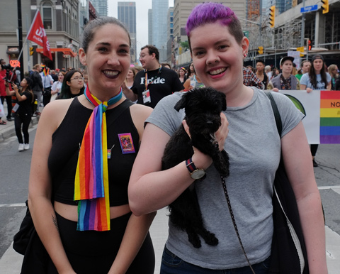dyke march 2018 - two women in the parade, one with short purple hair, carrying a small black dog