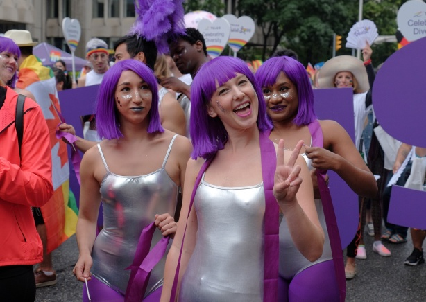 three women wearing tight silver bathing suits and purple wigs