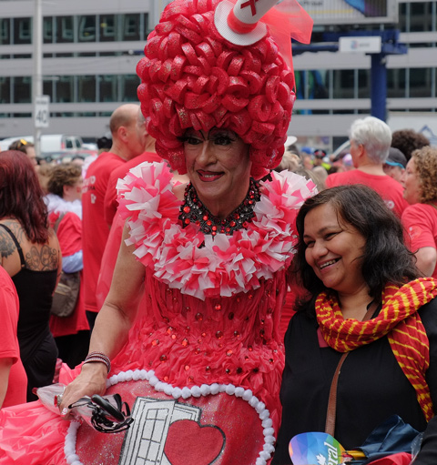 the Queen of Hearts, a drag queen in red with large red plastic wig and a red dress, posses for a pic with a woman