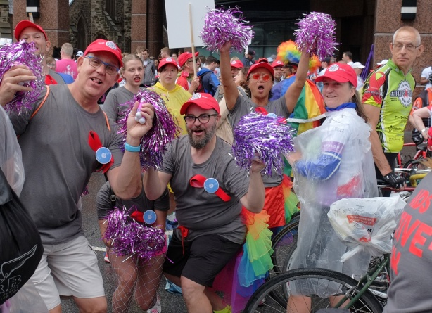 group with red hats and purple and silver sparkly pom pom things poses with cheers and waves for a picture before the pride parade begins