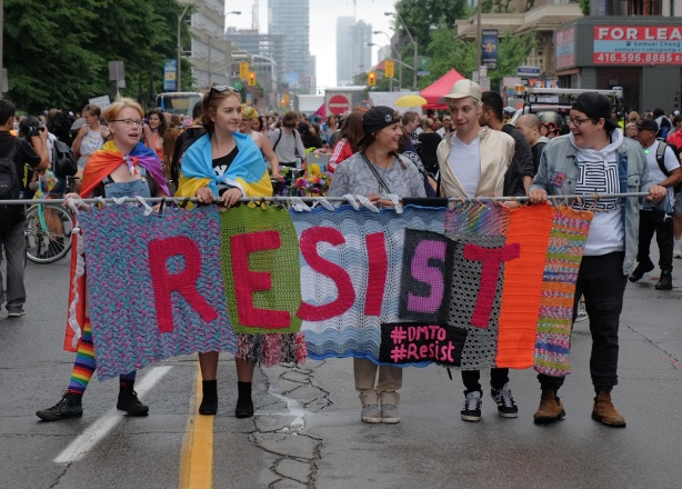 dyke march 2018 - a group of people carrying a banner made of yarn, crocheted, that says resist. #dmto #resist