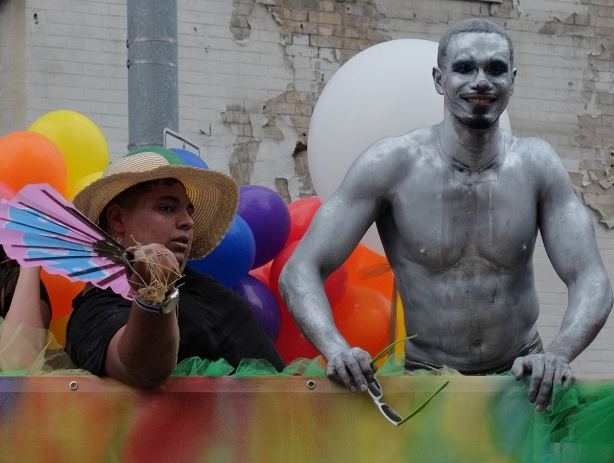 two men on a float at the pride parade, one is covered in silver paint, the other is seated and wearing a large brimmed hat and holding balloons