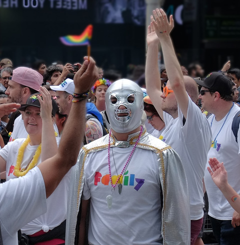 man in a silver mask covering his whole head, with a group in white t-shirts in the pride parade