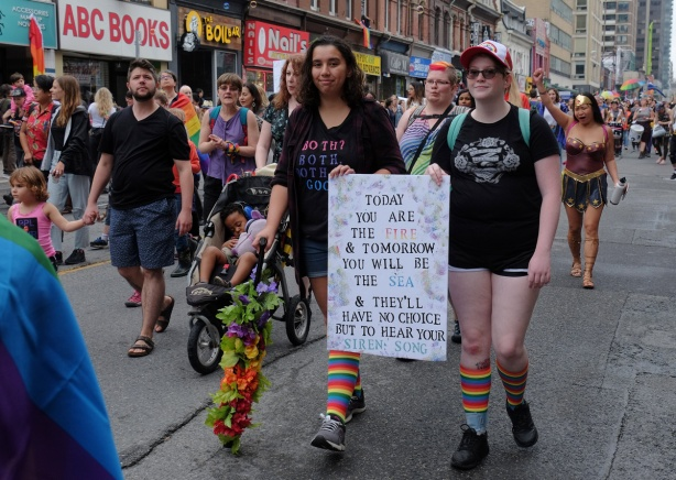 groups of people walking in dyke march 2018, two are holding a sign that says today you are the fire and tomorrow you will be the sea and they'll have no choice but to hear your siren song a sign that says