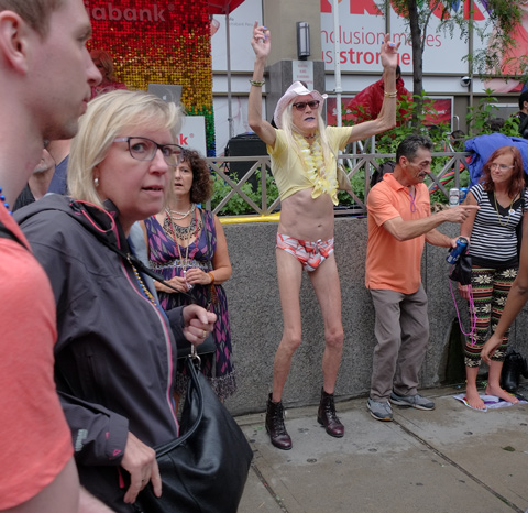 a very skinny man with grey hair, a yellow top and red skimpy short pants, other pwople wakling by on the sidewalk